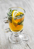 Green tea with lemon and a rumpled in a glass mug Royalty Free Stock Photo