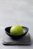 Green tea matcha ice cream scoop in bowl on a grey stone background. Copy space. Green tea matcha ice cream scoop in bowl on a grey stone background Royalty Free Stock Image