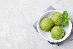 Green tea matcha ice cream scoop in white bowl on a grey stone background. Copy space Top view. Green tea matcha ice cream scoop in white bowl on a grey stone Stock Photos