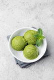 Green tea matcha ice cream scoop in white bowl on a grey stone background Copy space Top view. Stock Photo