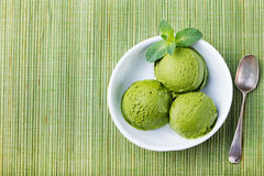 Green tea matcha ice cream scoop in white bowl on a wooden background Copy space Top view Stock Photo