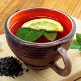 Green tea with meant and lemon. Hot drink in a rustic clay cup made of black tea, fresh mint leaves and lemon on a wooden table. Delicious healthy beverage made Royalty Free Stock Images