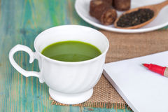 Green tea with milk or hot matcha latte with cane Stock Photos