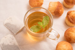 Green tea with mint  in a glass cup with vanilla muffins. Stock Photo