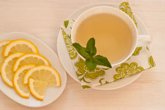 Green tea with mint and lemon. Green tea with fresh mint and lemon on antic wooden background, view from above Stock Photos