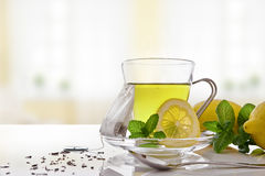 Green tea with mint and lemon with teabag front view Stock Images