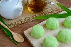 Green tea mochi flavored with bean filling and cup of tea on woo Stock Photos