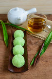 Green tea mochi flavored with bean filling and cup of tea on woo Royalty Free Stock Image