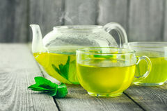 Green Tea. Mug of green tea and teapot on wood table royalty free stock photography