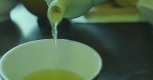 Green tea pouring from a teapot to a cup in Japan - closeup. Green tea pouring from a teapot to a cup - the tea is hot and steamy - in Japan - closeup stock video footage