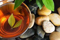Green tea river pebbles. Cup of green tea and multicolored pebbles Stock Photo