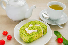 Green tea roll cake, tea cup and tea pot Stock Photo