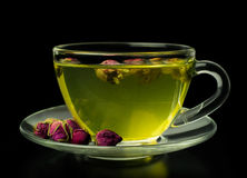 Green tea with rose buds in a glass cup Royalty Free Stock Photos