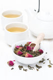 Green tea with rosebuds in a bowl, cups and teapot Stock Photography