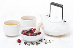 Green tea with rosebuds, cups and teapot on white wooden table Royalty Free Stock Photography