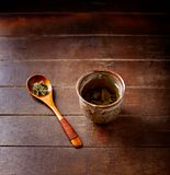 Green tea sencha in a traditional, japanese tea cup and sencha leaves on a wooden  tea spoon. Dark wooden background. Stock Image