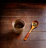 Green tea sencha in a traditional, japanese tea cup and sencha leaves on a wooden  tea spoon. Dark wooden background. Stock Photo