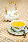 Green tea serving. Cup of green tea and a teapot on a table-cloth (focus on a cup royalty free stock photos