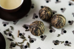 Green tea and small balls bundle of dried green tea leaves. Small bowls of green tea and small balls bundle of dried tea leaves on Japanese pattern tablecloth royalty free stock image