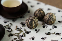 Green tea and small balls bundle of dried green tea leaves. Small ceramic cups of green tea and small balls bundle of dried tea leaves on Japanese pattern royalty free stock photography