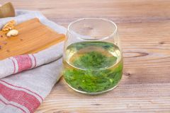 Green Tea with Some Nuts. On wooden table Royalty Free Stock Images