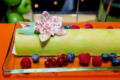 Green Tea Swiss Roll Cake on glass dish with fresh berries, rasb Stock Photography