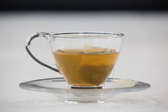 Green tea with tea bag in cup. Against white background Stock Image