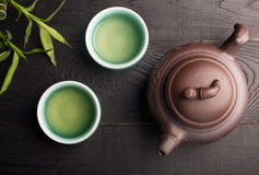 Green tea in the tea cups. Asian clay teapot with glazed clay bowls for green tea stock images