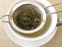 Green tea in tea strainer Stock Images
