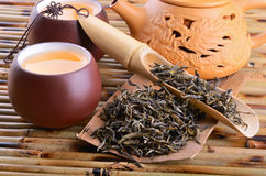 Green tea. Teapot and aromatic oolong tea leaves on bamboo mat background Royalty Free Stock Image
