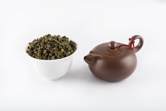 Green tea and teapot. Green tea leaves and clay teapot on white background. Isolated Stock Photos