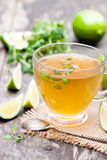 Green tea with thyme and lime on rustic wooden background Stock Photo