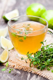 Green tea with thyme and lime on rustic wooden background Royalty Free Stock Photography