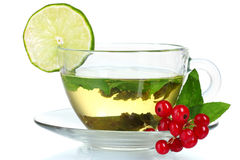Green tea in transparent cup with lime and berry Royalty Free Stock Photography