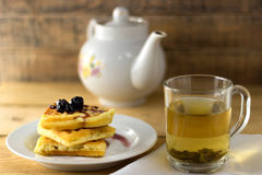 Green tea in a transparent mug with waffle. Waffles with jam and green tea on a wooden background Stock Images