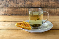 Green tea in a transparent mug with waffle. On a wooden background Stock Photo