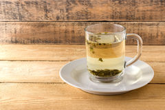 Green tea in a transparent mug. On a wooden background Stock Photo