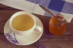 Green tea in a white cup and jar of honey with spoon and blue ki Stock Photography