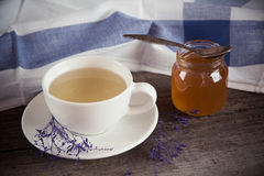 Green tea in a white cup and jar of honey with spoon and blue ki Stock Photo