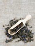 Green tea and wooden shovel on linen background Stock Photo