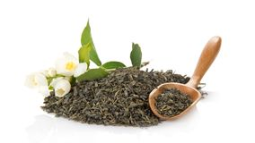 Green tea, wooden spoon and blossoming jasmine Stock Photo