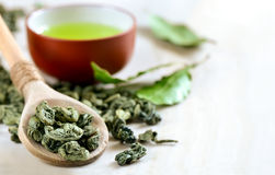 Green tea. Wooden spoon with dried green tea leaves in it and a cup of green tea on a backstage Royalty Free Stock Photos