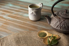 Green tea. In a wooden spoon with rustic teapot and ceramic cup Royalty Free Stock Photos