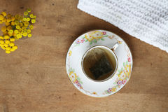 Green Tea and Yellow Flowers. Green tea in a vintage teacup with yellow flowers on a wooden tabletop stock photography