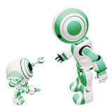 Green Teacher Robot. A conceptual image of a green colored parent robot training a baby robot, on a white background Stock Image