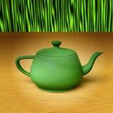 Green teapot on a bamboo mat Stock Photography