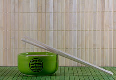 Green teapot and chopsticks against straw mat Royalty Free Stock Photography