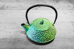 Green teapot on grey wooden background Stock Images