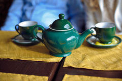 Green teapot and two cups of tea Royalty Free Stock Photo