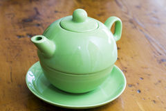 Green teapot on a wooden kitchen surface Stock Image